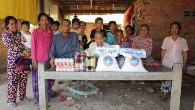Bun Sen sentada em frente a mesa com irmãos, rodeados por outros parentes em varanda de casa