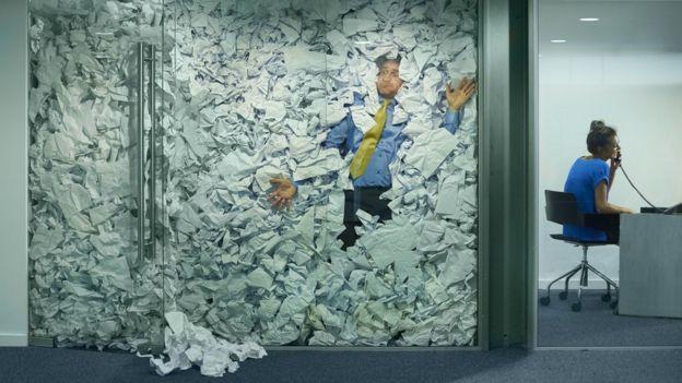 Hombre atrapado en una oficina repleta de papeles.