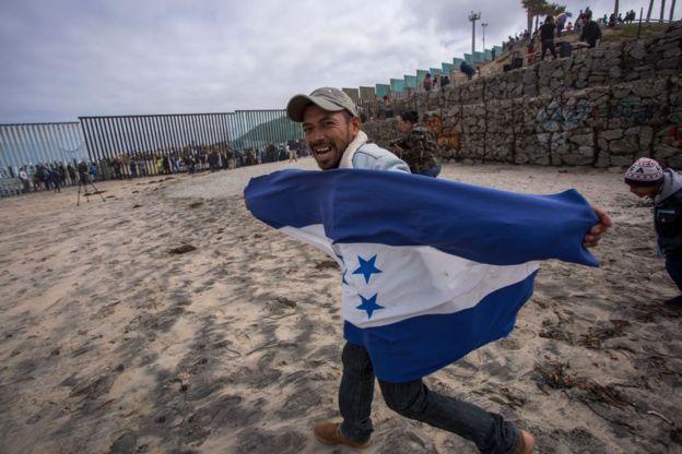 Personas sobre la reja que marca la frontera entre México y Estados Unidos