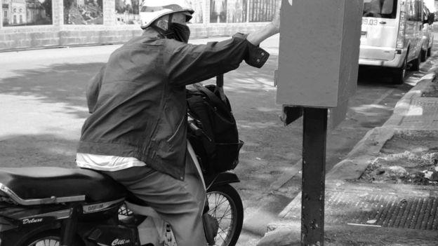 Một cụ già ngoài 70 vội gửi nhanh một lá thư vào thùng.