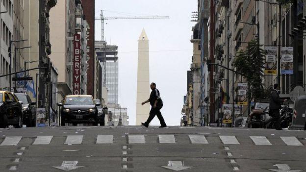 Un hombre cruza la calle con el Obelisco de fondo.
