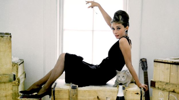 Audrey Hepburn lies on a packing case with her cat in the iconic black dress from Breakfast at Tiffany's