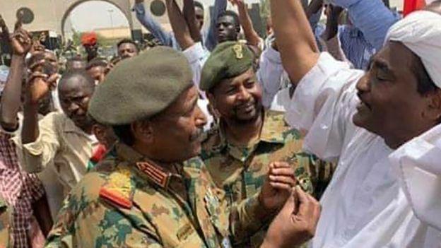 Gen Abdel Fattah Abdelrahman Burhan talks to demonstrators in Khartoum, 12 April