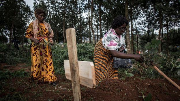 Des membres de la famille déposent des feuilles sur la tombe d'un parent décédé d'Ebola à Butembo.