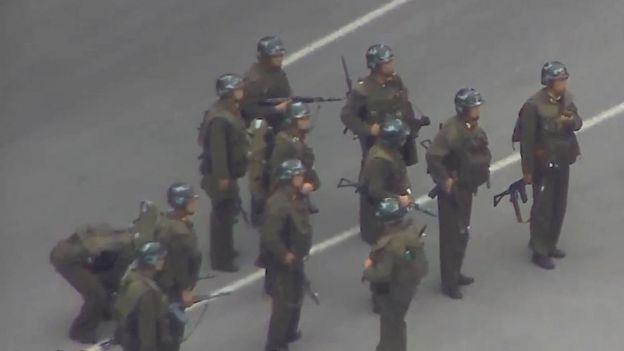 سرباز کره شمالی که در منتهیالیه سمت چپ عکس دیده میشود سلاحش را برای دقایقی زمین گذاشت