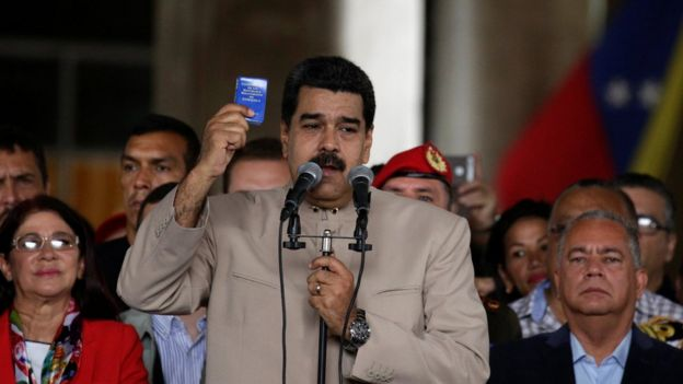President Nicolás Maduro holds the Venezuelan constitution as he calls for change