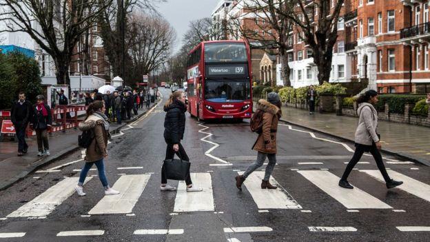Beatles' fans cross Abbey Road zebra crossing