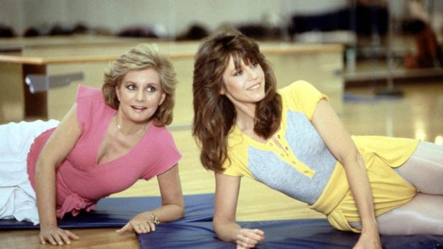 Jane Fonda and another woman exercising on the floor