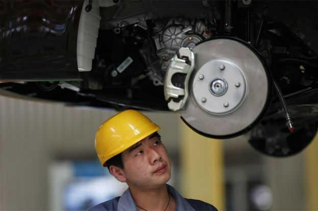 An employee looks at a vehicle in the process of being assembled at the Geely plant in Cixi, in the Chinese province of Zhejiang, on June 21, 2012.