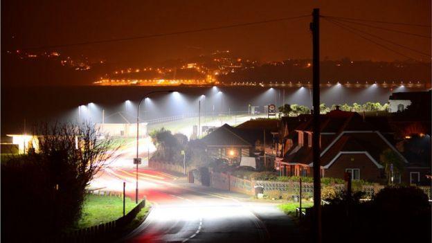 Postes de luz iluminando una carretera.