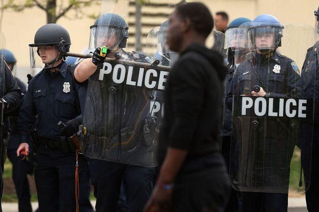 Policía apunta a un hombre negro con un arma Taser.