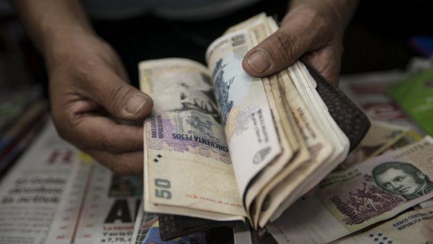 Una persona cuenta pesos argentinos.