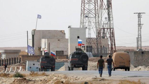 Menbic yakınlarında Suriye ve Rusya bayraklarıyla devriye gezen askeri araçlar