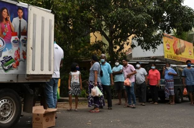 People line up to buy milk from a vendor along a street during a government-imposed nationwide lockdown as a preventive measure against the COVID-19 coronavirus in Colombo on March 30, 2020.