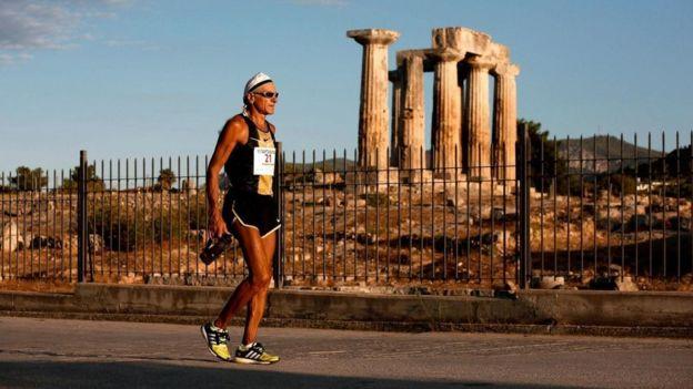 أحد العدائين المشاركين في ماراثون إسبرطة 2013 يتقدم بهدوء متجاوزا أحد معابد كورنثوس القديمة