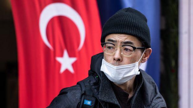 İstanbul'da, sokakta maskeyle gezen bir kişi.