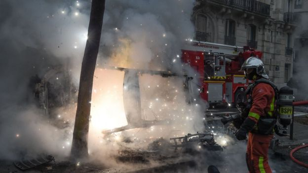 A fireman stands next to a vehicle set on fire by protesters during Paris riots, 8 December 2018