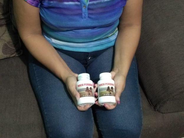 """Foto mostra mulher segurando frascos de produto onde se vê um casal sentado e se lê """"Maca Peruana"""""""