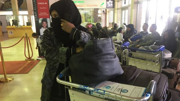 Woman covering her face in an airport