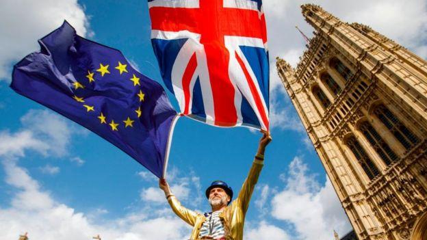 Un hombre sostiene la bandera de Reino Unido y la UE frente al parlamento británico