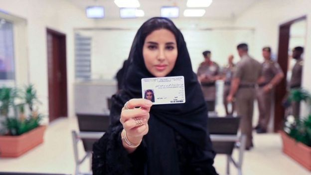 A woman shows her Saudi driving license