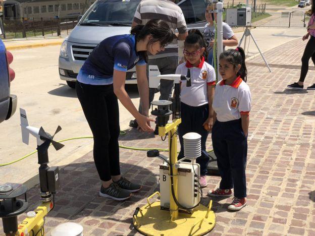 Una científica con alumnos y un pod.