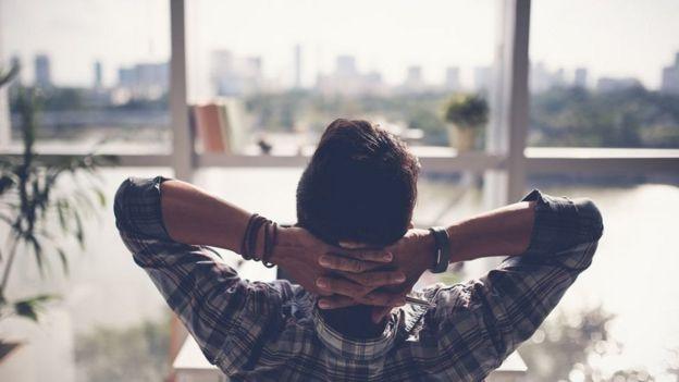 Homem descansando de frente para a janela do escritório