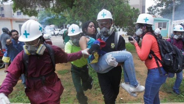 Una joven es cargada tras sufrir los efectos de gases lacrimógenos en una protesta en Maracaibo, el 18 de mayo de 2017