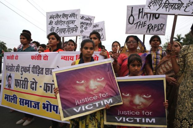 People hold posters and candles during a march to protest against the rape of a seven-year-old girl in Mandsaur.