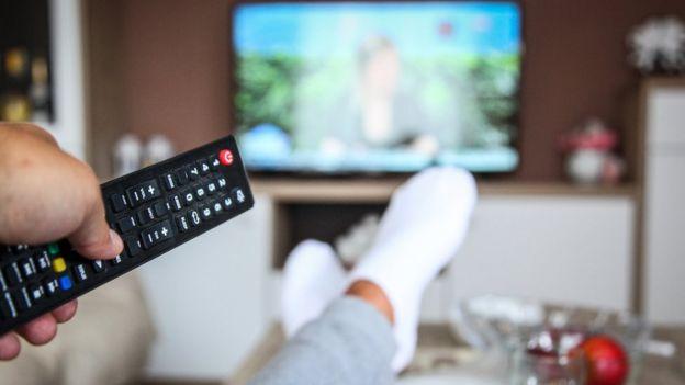 Homem assistindo à TV