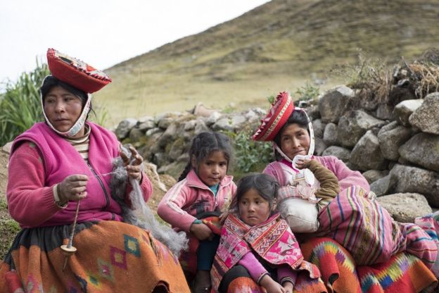 Quechua women and two young girls pose for the camera in the stunning, handmade clothing, Lares Valley, Peru, May 2016.
