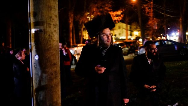 """Jewish people try to take a look of the area where 5 people were stabbed at a Hasidic rabbi""""s home in Monsey"""