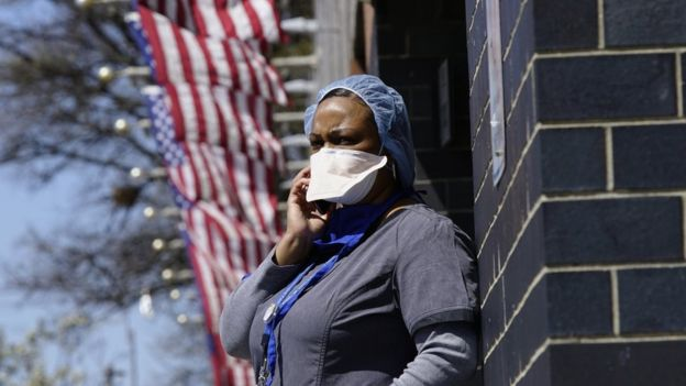 A health-care worker in Queens borough New York City talks on her mobile phone outside the hospital.