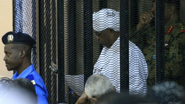 Sudan's deposed military ruler Omar al-Bashir stands in a defendant's cage during the opening of his corruption trial in Khartoum on August 19, 2019