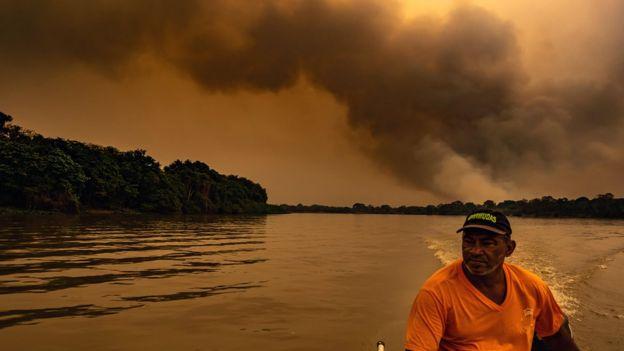 Pescador anda em barco com grande nuvem de fumaça ao fundo
