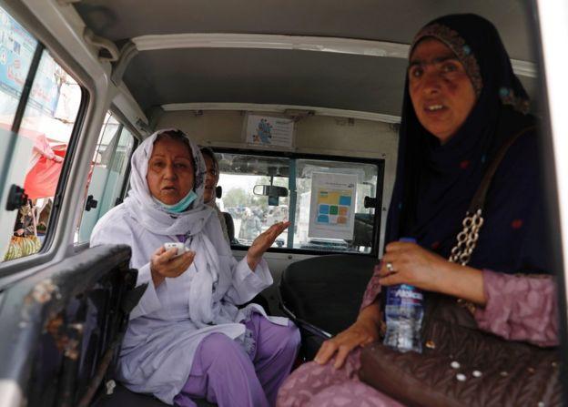 Dos mujeres rescatadas esperan dentro de una ambulancia.