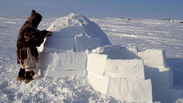An Inuit man building an igloo