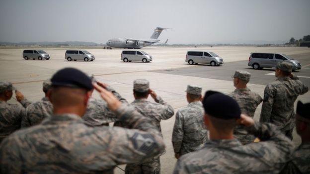 Soldados americanos saludam veículos transportando restos mortais