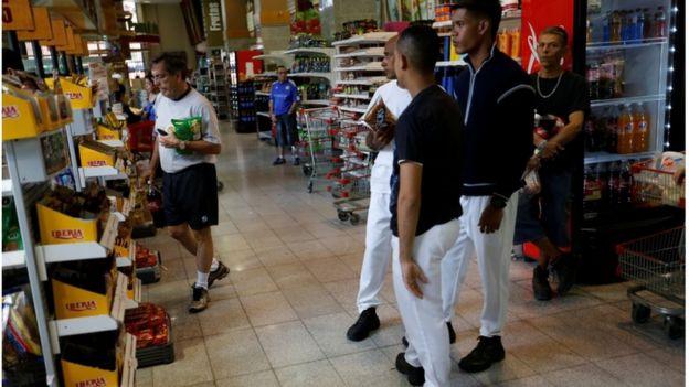 personas hacen compras en el supermercado