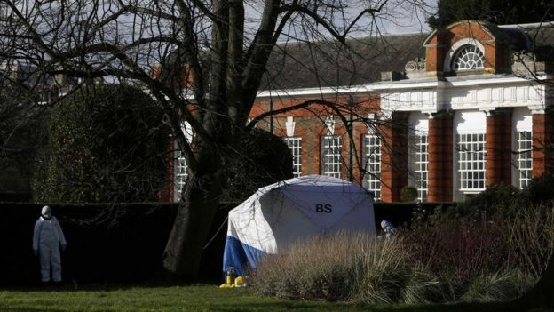 Forensic police officers stand by a forensic tent near the grounds of Kensington Palace