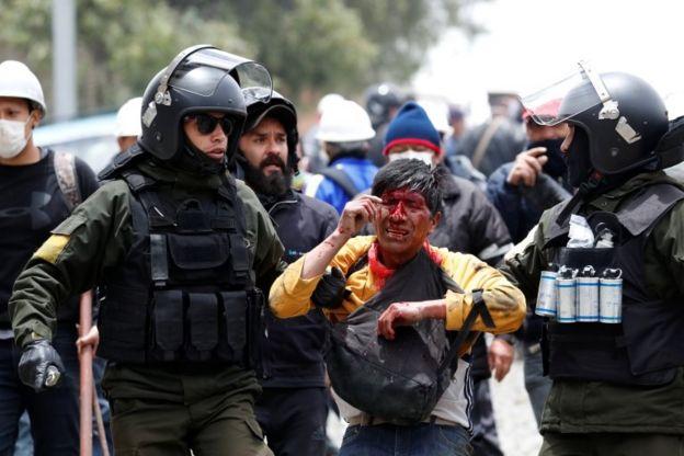 Manifestante ensanguentado é escoltado por policiais na rua