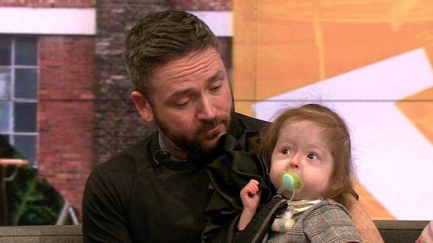 Isla en brazos de su padre.
