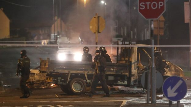 Police in riot gear patrol past a burnt-out vehicle during the violence in Londonderry