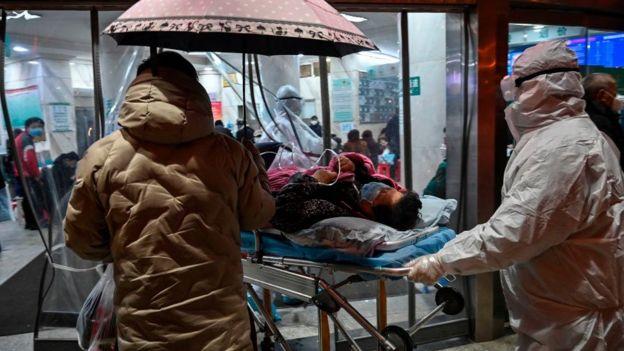 Một bệnh nhân được đưa đến bệnh viện Chữ Thập Đỏ Vũ Hán khi bên trong có hàng dài người ngồi xếp hàng chờ khám bệnh hôm 25/1