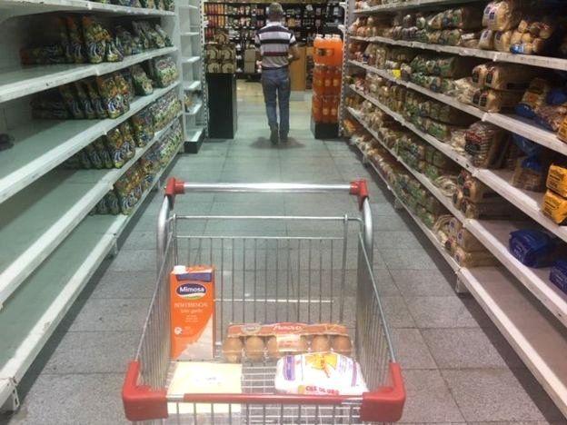 Carrinho de compras com itens como leite e ovos
