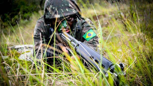 Militar com arma em punho