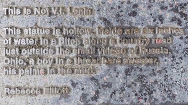 Một tấm bảng nhỏ đặt bên cạnh với nhiều thông tin liên quan đến bức tượng