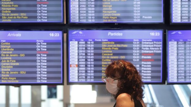 Passageira com máscara perto do telão que mostra os embarques e desembarques do aeroporto internacional de Viracopos, em Campinas