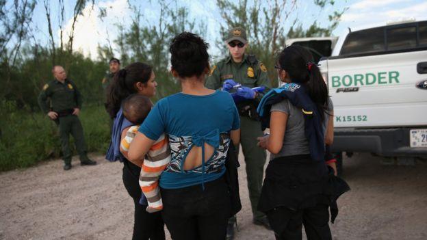 Mujeres hablan con un agente fronterizo
