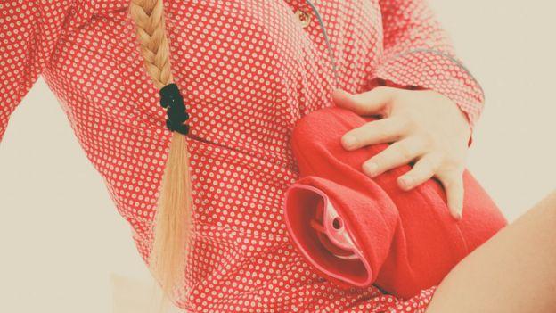 Mujer con cólicos menstruales con una bolsa de agua caliente.